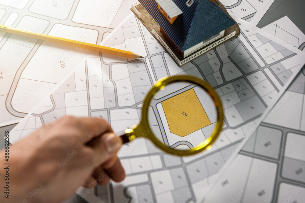 Fototapeta searching building plot for family house construction - hand with magnifier on cadastre map