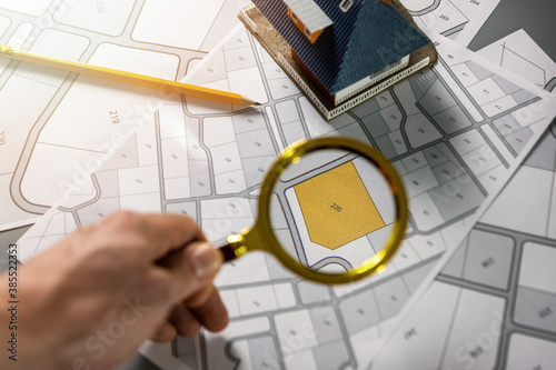 Obraz searching building plot for family house construction - hand with magnifier on cadastre map - fototapety do salonu