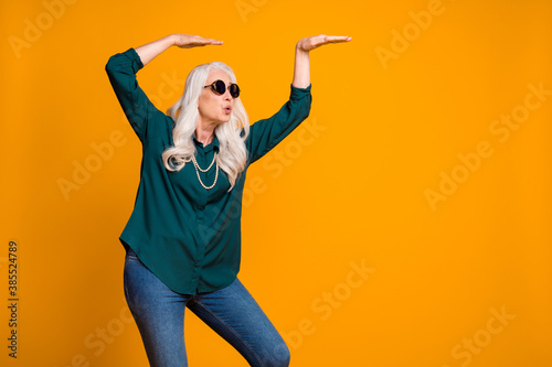 Photo of crazy grandma lady music lover senior retro party cool look dancing strange youngster moves wear green shirt sun specs pearls necklace jeans isolated bright yellow color background