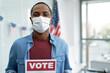 Leinwandbild Motiv Black man in face mask with voting card