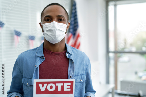 Obraz Black man in face mask with voting card - fototapety do salonu