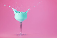 Mint Creme Cocktail Splashing On A Pastel Pink Background With Space For Text