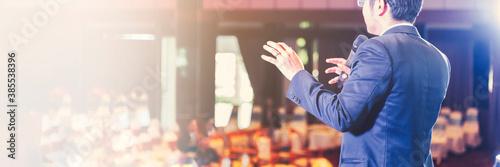 Billede på lærred Asian businessman giving speech presentation stage meeting hall conference profe