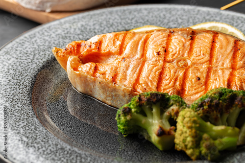 Grilled salmon steak with broccoli on grey plate Canvas Print