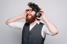 Bearded Cheerful Young Man Is Listening To The Music With Headphones On Holding Them With Both Of His Hands Near A White Wall