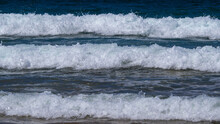 Close-up Image Of A Series Of Three Small Waves Approaching Shore