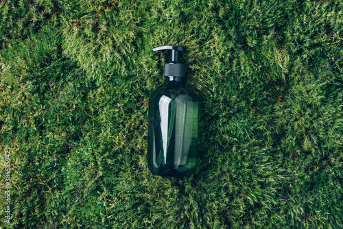Unlabelled cosmetic bottle on green moss background. Biophilic design. Skin care, organic body treatment, spa concept. Vegan eco friendly cosmetology product. Organic cosmetics.
