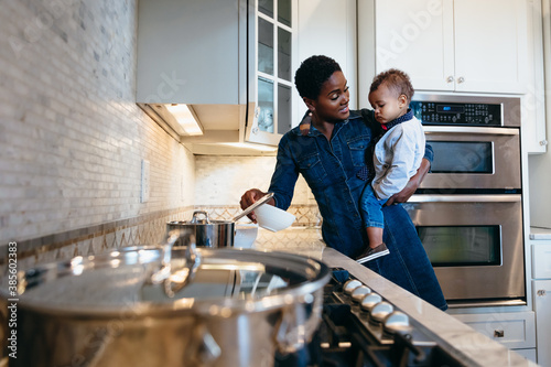 Black mother and son in kitchen preparing food for family dinner - 385602383