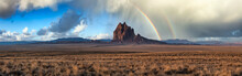 Dramatic Panoramic Landscape View Of A Dry Desert With A Mountain Peak In The Background. Dramatic Sunrise With Rainbow Artistic Render. Taken At Shiprock, New Mexico, United States.