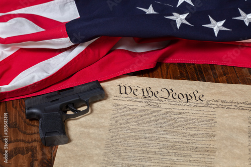 Modern pistol with thirteen star flag and the constitution of the United States on dark wood background #385613191