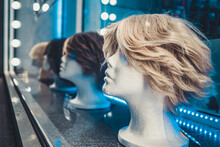 White Foam Female Mannequins Heads In A Row On A Store Window At Night. Blue And White Neon Lights And Glare On Glass. Nightlife Of The Metropolis.