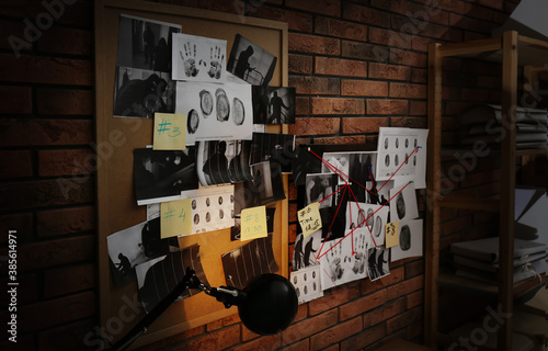 Photo Boards with fingerprints, crime scene photos and red threads on brick wall