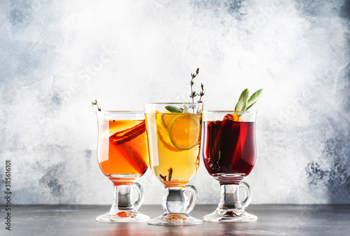 Obraz Mulled wine from red and white wine and hot mulled cider. Autumn or winter drinks and cocktails in glass mugs with spices and citrus fruit - fototapety do salonu