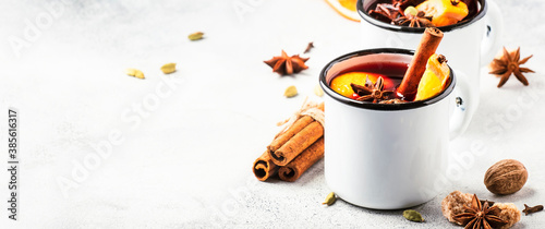 Obraz Mulled wine in white metal mugs with cinnamon, spices and orange on gray background, traditional drink on winter holiday. Copy space - fototapety do salonu