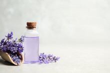 Bottle Of Essential Oil And Lavender Flowers On Light Stone Table. Space For Text