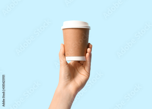 Obraz Woman holding takeaway paper coffee cup on light blue background, closeup - fototapety do salonu