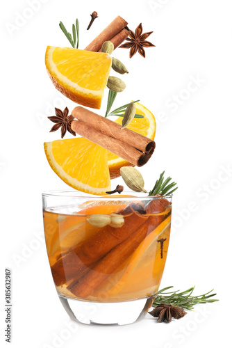 Obraz Cut orange and different spices falling into glass of mulled wine on white background - fototapety do salonu