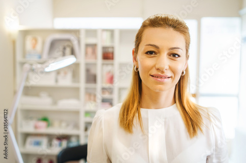 Fototapeta Front view on adult caucasian woman beautician doctor at spa - female professional cosmetologist standing at work in salon in day - healthcare and beauty concept obraz