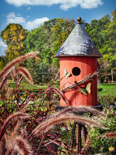 Red Birdhouse With Butterflies In A Flower Garden On A Beautiful Sunny Blue Sky Day In Wisconsin
