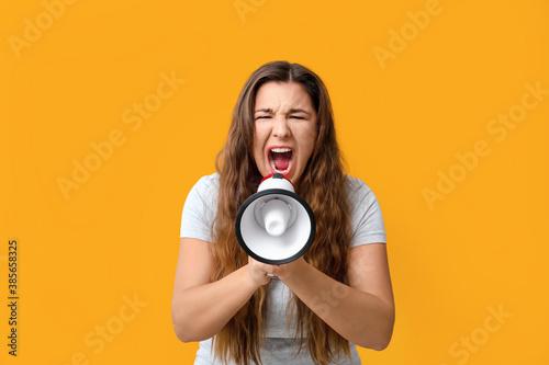 Obraz na plátně Protesting woman with megaphone on color background