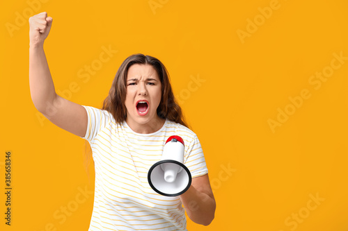 Fototapeta Protesting woman with megaphone on color background
