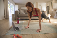 Woman Performing Exercise While Looking At Laptop  At Home