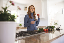 Woman Holding Vegetables And Knife In The Kitchen