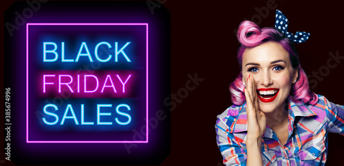 Beautiful happy excited woman holding hand near open mouth. Girl dressed in pin up. Blond model at retro fashion vintage concept, over dark background. Black Friday sales neon light sign.