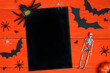 Leinwandbild Motiv Halloween holiday background with blank black card and decorations on orange wooden boards. Festive frame with bats, skeletons, spiders and copy space.
