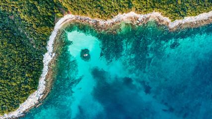 Drone view of the seashore with a boat at Cisterna beach Rovinj Croatia