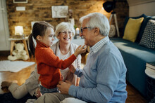 Cute Small Girl Spending Time With Her Grandparents At Home.