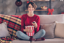 Photo Of Charming Young Lady Hold Remote Control Popcorn Bucket Sitting Couch Wear Red Pullover Jeans Socks Indoors
