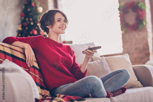 Obraz Photo of lovely young lady hold remote control sitting sofa toothy smile wear red pullover jeans socks indoors - fototapety do salonu