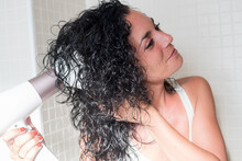 Young Woman In Profile Smiling Curling Her Hair With A Hairdryer With A Special Nozzle For Curling Her Hair. Dryer With Diffuser. Care And Beauty Concept.