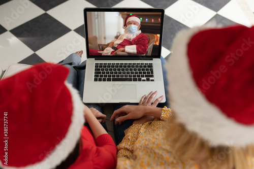 Woman and daughter in Santa hats having a video chat with Santa Claus in face mask on laptop