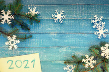 Snowflakes On Blue Background Wich Christmas Branches With 2021 Over White Background - Represents The New Year 2021