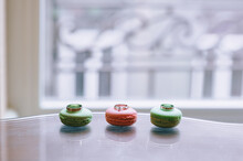 Close Up Of Wedding Rings Lying On Sweet Macaroons On Window Background. Daylight.