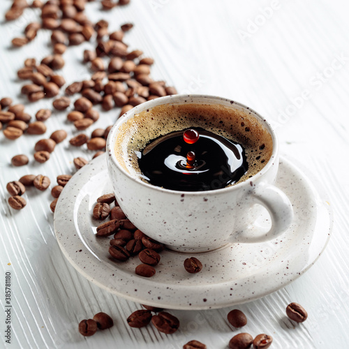 Obraz Black coffee and coffee beans on a white wooden table. - fototapety do salonu