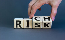 Take A Risk And Getting Rich Concept. Hand Flips A Cube And Changes The Word 'risk' To 'rich' Or Vice Versa. Beautiful Grey Background. Business Concept. Copy Space.