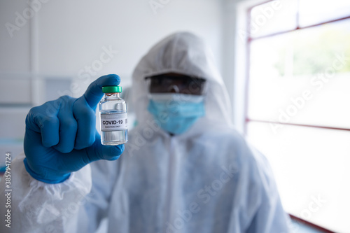 Health worker wearing protective clothes holding a vial bottle with Covid-19 text