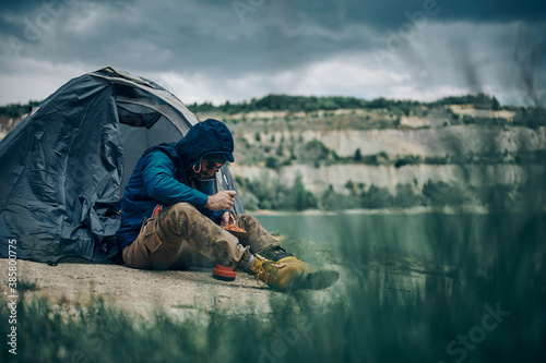 Fotografiet Bearded man in jacket sitting near tent on camping trip and heating his lunch on rainy weather
