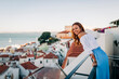 Young woman smiling while standing at rooftop at Alfama, Lisbon, Portugal