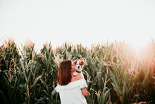 Rear View Of Young Woman With Dog At Cornfield During Sunset