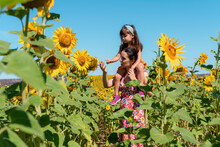 Single Mother Carrying Daughter On Shoulders In Sunflower Field
