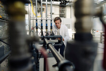 Scientist At Pipework In A Gre...