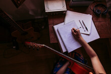 Young Woman Writing In Book While Practicing Guitar At Table