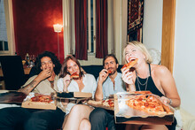 Happy Friends Enjoying Pizza While Sitting On Sofa During Party At Home