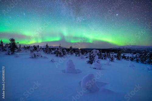 Northern lights over snow-covered landscape at dusk