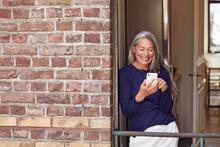 Smiling Woman Using Phone In B...