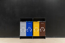 Colorful Garbage Bins With Recycling Symbols Against Black Wall In Corridor
